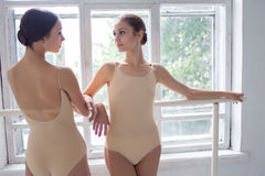 The two classic ballet dancers posing at barre Stock Photography