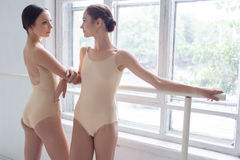 The two classic ballet dancers posing at barre Stock Photos