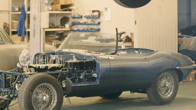 Two Classic Cars in a Workshop. Camera Moving Down stock footage