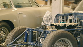 Two Classic Cars in a Workshop. Camera Moving Right. Motor vehicles in a renovation workshop. Close-up. Shot on RED Epic stock video footage