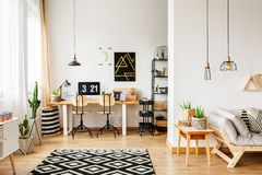Scandinavian style workspace with table. Two classic chairs at table with laptop and lamp in scandinavian style workspace with pillows on sofa Stock Photos