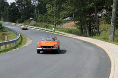Two classic orange italian sports cars on road royalty free stock photos