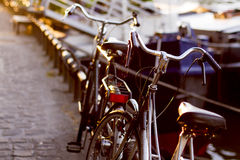 Two classic retro bicycles on cobblestone path. On the banks of the Seine River in Paris with sunlight from the sunset Stock Photography