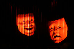 Two classic theatrical mask of tragedy and comedy. Lighting to a red curtain in the dark Royalty Free Stock Photos