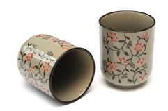 Two clay cups with red floral engraving design royalty free stock photos