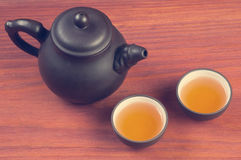 Two clay glazed tea bowls with brewed pu-erh tea and clay teapot on red wooden table vintage filtered. With place for text royalty free stock photography
