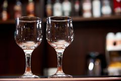 Two clean empty glasses on a blurred background of the bar stock photos