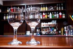 Two clean empty glasses on a blurred background of the bar royalty free stock photos
