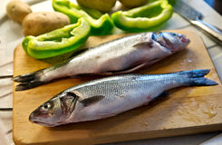 Two cleaned sea bass on a wooden board Royalty Free Stock Image