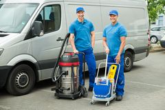 Two Cleaners Standing With Cleaning Equipments. Two Happy Male Cleaners Standing With Cleaning Equipments In Front Van royalty free stock image
