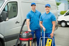 Two Cleaners Standing With Cleaning Equipments Royalty Free Stock Image