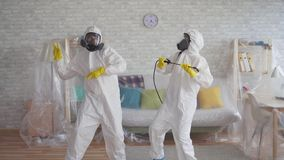 Two workers cleaning service or scientists in protective overalls dancing