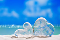 Two clear glass hearts on white sand beach, Royalty Free Stock Images