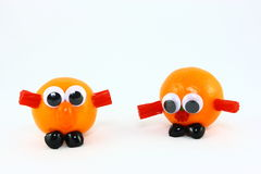 Two Clementines With Funny Faces. Two fresh clementine fruits decorated with plastic eyes and assorted candies to create fun fantasy creatures Royalty Free Stock Photos