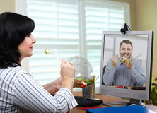 Two clerks eating together online Royalty Free Stock Photo