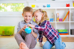 Two clever children exploring globe Stock Image