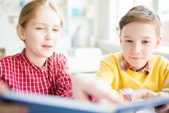 Lesson of literature. Two clever kids reading curious story in book before lesson of literature at school Stock Photo