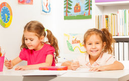 Two clever schoolgirls writing at the copybook Royalty Free Stock Photo