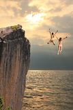 Two cliff jumping girls, coastal landscape. Two girls jumping from cliff rock, coastal landscape in the evening Royalty Free Stock Photo