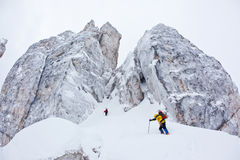 Two climbers approach to a winter steep face Stock Images