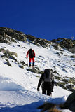 Two climbers ascending on Peleaga peak, in Retezat mountains, Romania. During a very cold and sunny day of winter two climbers are trying to get on top of Royalty Free Stock Images