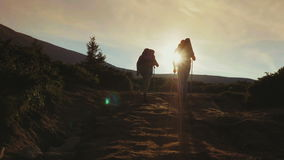 Two climbers climb up the mountain in the sun. Concept - wins and achievements. A couple of tourists with backpacks and trekking sticks descend down the mountain stock video