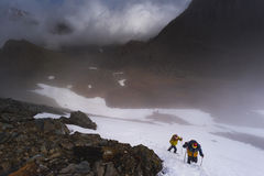 Two climbers in the mountains rise. Clouds Royalty Free Stock Photography