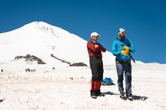Two climbers talk on training on the right slip on the slope with an ice ax for non-stop braking against the background royalty free stock photos