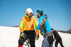 Two climbers talk on training on the right slip on the slope with an ice ax for non-stop braking Royalty Free Stock Photos