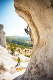 Two climbers are training. Two climbers are trained on a large boulder. Extreme sport. Active recreation in nature. A women overcomes a difficult climbing route Royalty Free Stock Photos