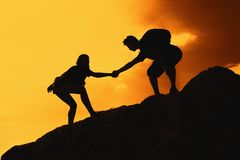 Two climbing people in mountains as symbol for help and success. Outdoor on sunset stock images