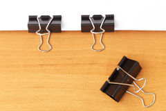 Two clips stapling papers. On the table Stock Photography