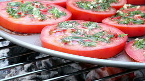 Two clips of tomato slices on barbecue grill. Two clips of tomato slices with herbs and olive oil frying in a pan on a barbecue grill on a sunny day stock video