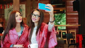 Two close friends do selfie in the cafe. Two close girlfriends want to make a selfie in the cafe on memory stock footage
