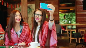Two close friends do selfie in the cafe. Two close girlfriends want to make a selfie in the cafe on memory stock video footage