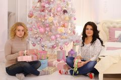 Two close friends share pleasant emotions and festive gifts, sit royalty free stock images