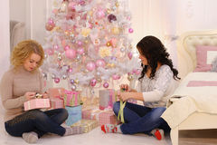 Two close friends share pleasant emotions and festive gifts, sit stock photos