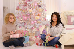 Two close friends share pleasant emotions and festive gifts, sit Stock Images
