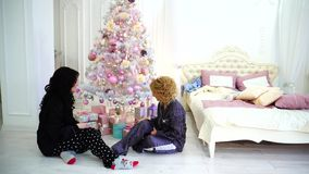 Two close friends share pleasant emotions and festive gifts, sitting on floor in bright bedroom near bed and Christmas. Lovely girls decorate Christmas tree and stock video