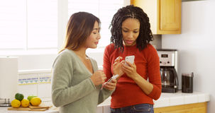 Two close friends using mobile phones and leaning against kitchen counter Stock Photo