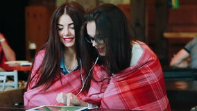 Two close friends watching something on a tablet. Two young and beautiful girl sitting at the table watching something on a tablet stock footage
