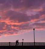 Two close people walking on a bridge, in the evening Royalty Free Stock Image