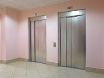 Two closed elevators in a business lobby Royalty Free Stock Photos