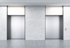 Two closed elevators in corridor with concrete walls Stock Images