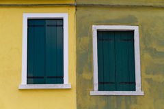 Two closed green windows on a yellow wall Stock Image