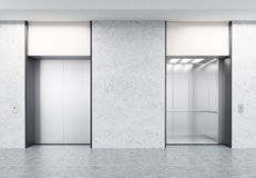 Two closed and open elevators in corridor with concrete walls Royalty Free Stock Image