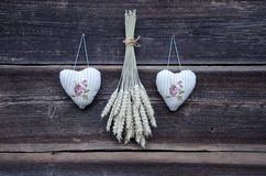 Two cloth hearts symbols and wheat ears bunch on wall Stock Photography