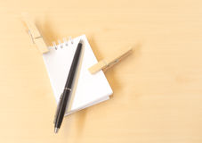 Two Clothespins with Black Pen and White Notepad. Two Clothespins with Black Pen and a White Notepad on Wooden Table Stock Photos
