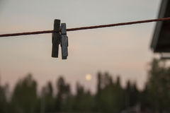 Two clothespins. Hanging on a line with the moon behind Stock Photo