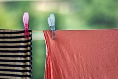 Two clothespins and laundry on clothesline Stock Photo
